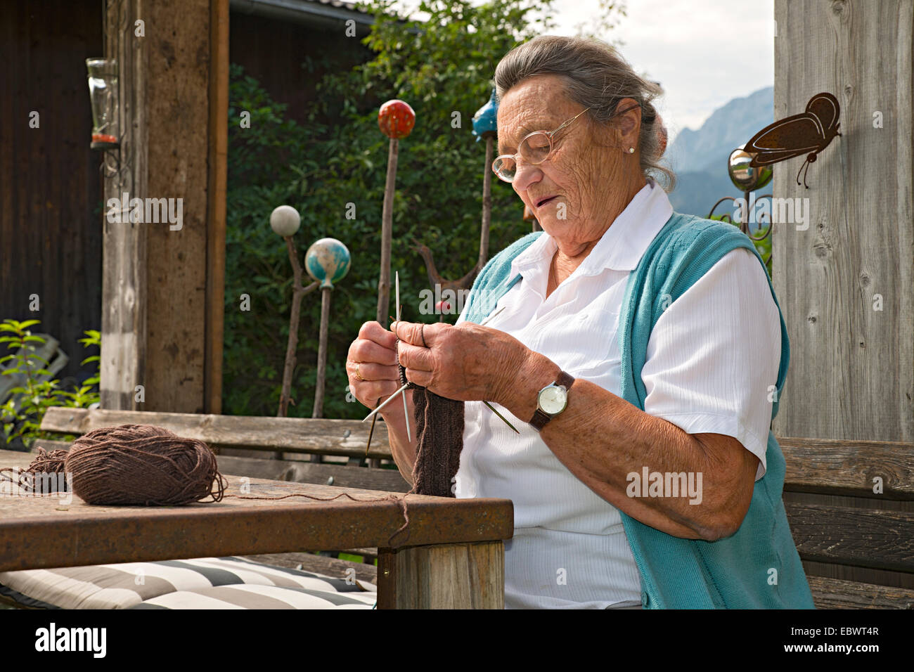 Farmer working on the farm, knitting leg warmers, Kreutner family farm, Schwaz District, Tyrol, Austria Family - Stock Image