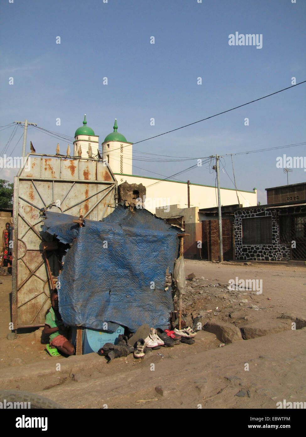 primitive little shop in which shoes are repaired with a mosque in the background, Burundi, Bujumbura mairie, Bwiza, Stock Photo