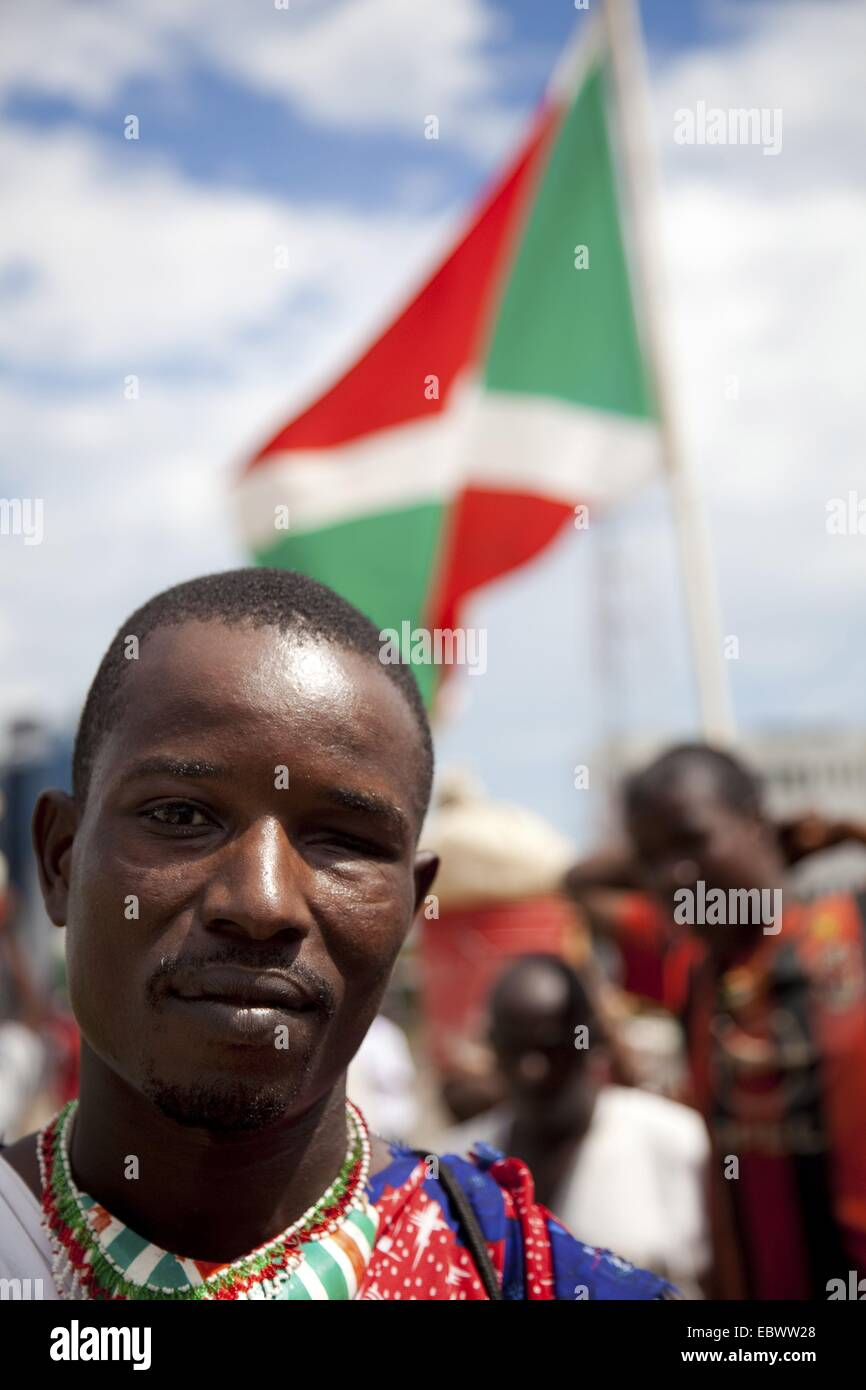 veteran soldier of the rebels who lost an eye in the cicil war is standing in front of a Burundian national flag - Stock Image