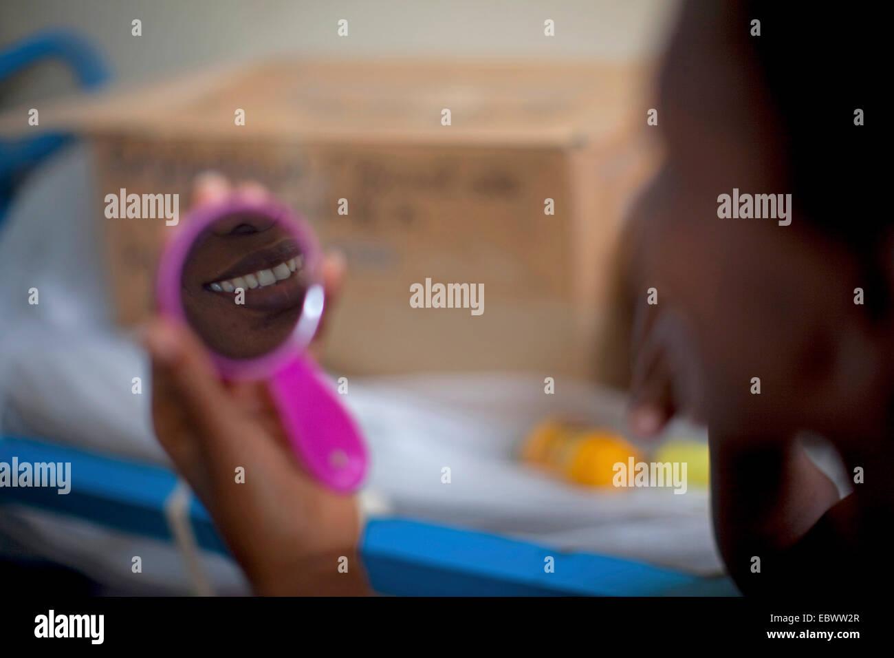 mouth of woman mirroring in pocket mirror, Burundi, Bujumbura - Stock Image
