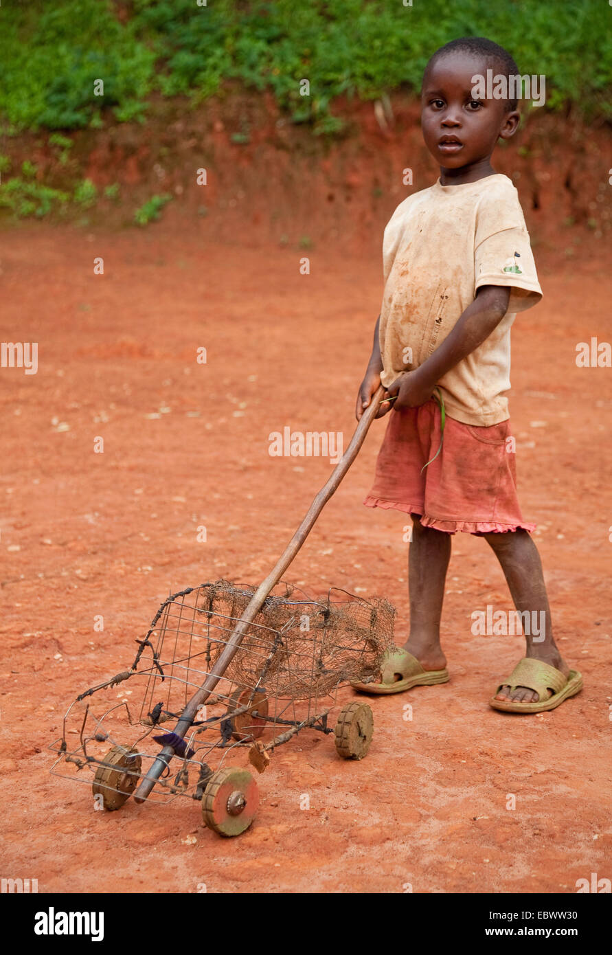 boy playing with selfmade wire frame toy car, Burundi, Gitega - Stock Image