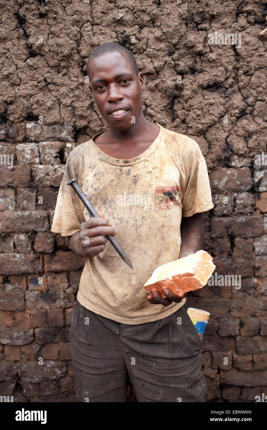 worker with clay brick and bit standing in front of a wall, Burundi, Karuzi, Buhiga - Stock Image
