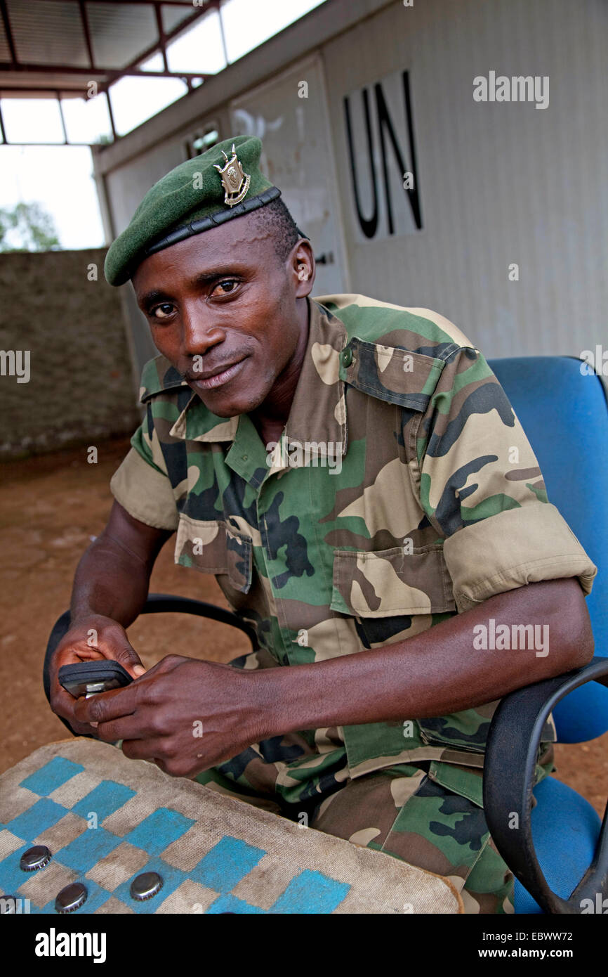 soldier responsible for the security of a field buero of the UN is playing draughts with a fellow between containers - Stock Image
