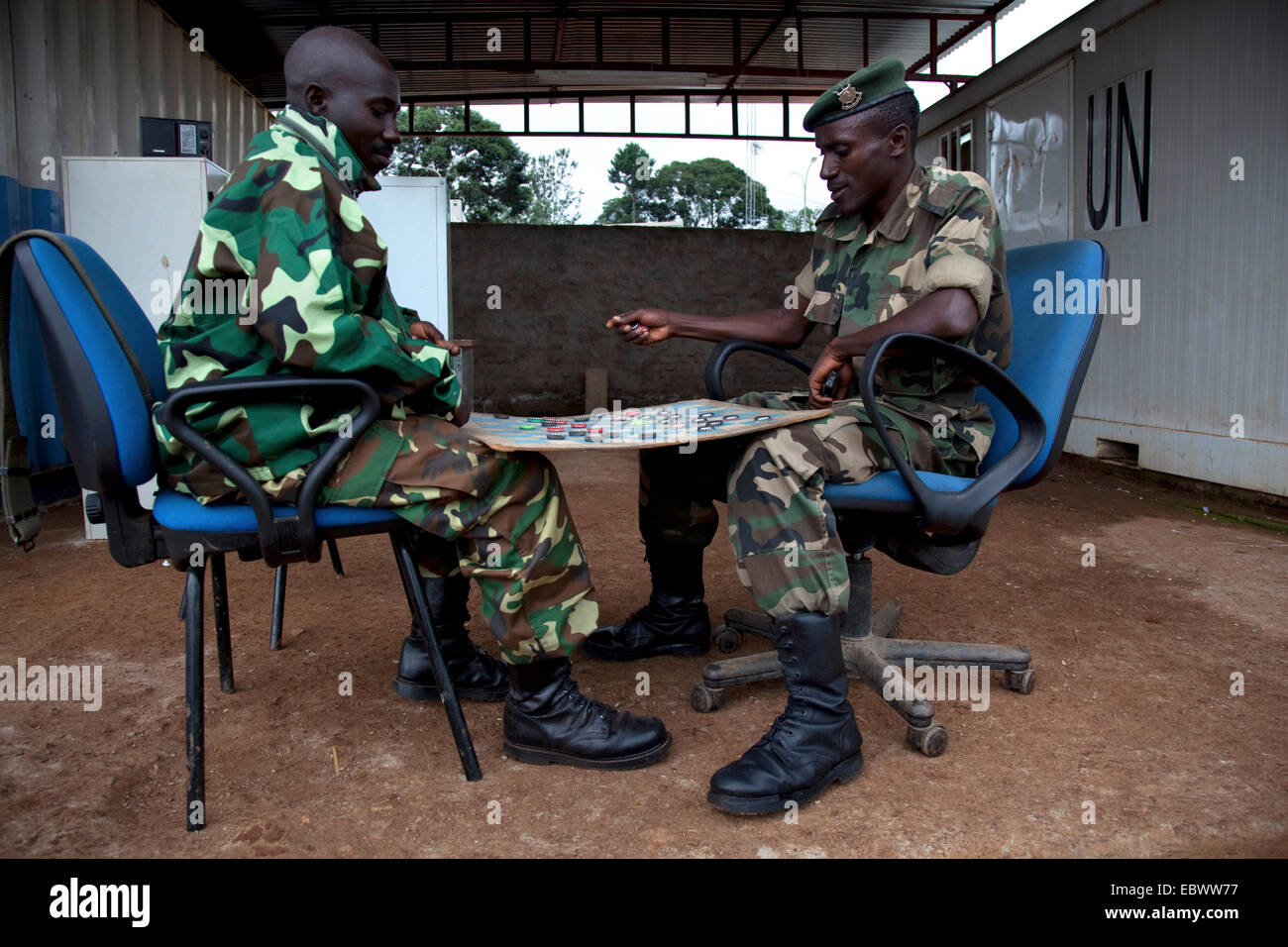 two soldiers responsible for the security of a field buero of the UN are playing draughts between containers with - Stock Image
