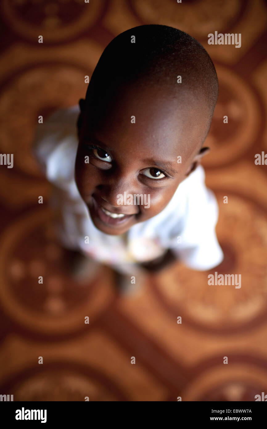 little boy standing on a tiled floor looking up at the camera over his head with a smile, Burundi, Bujumbura Mairie, - Stock Image