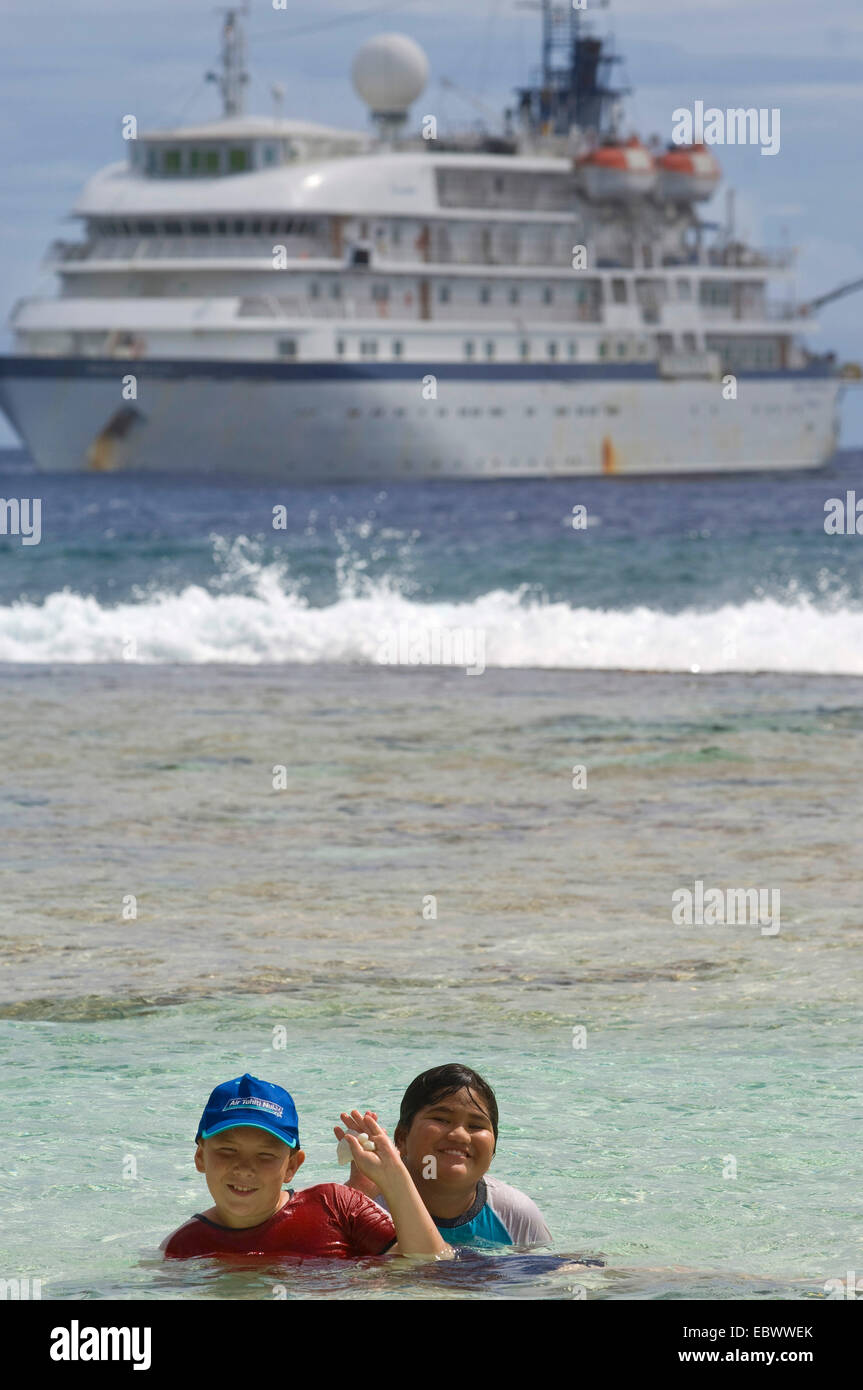 Cruise ship anchored off island with islanders in the water, Cook Islands, Atiu - Stock Image