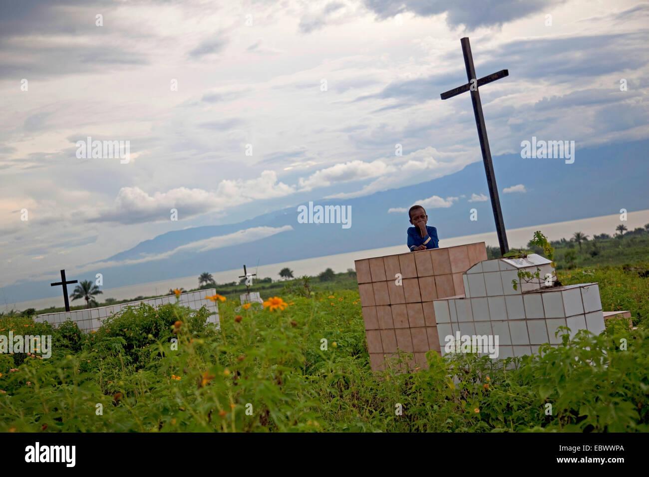 little boy at savaged graves on cemetery near Lake Tanganyika, Burundi, Bujumbura Mairie, Bujumbura - Stock Image