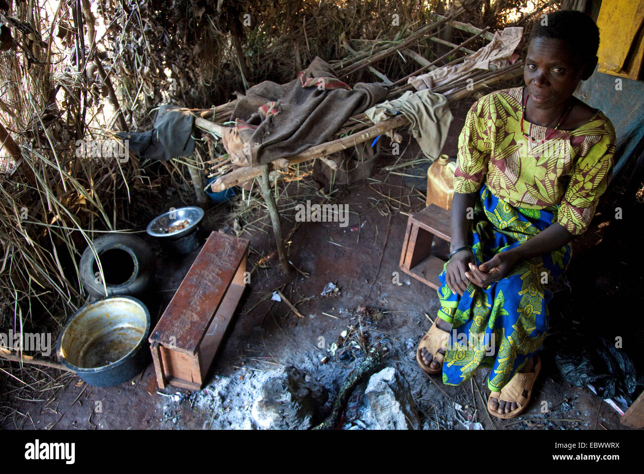 widowed mother of two children, member of the Batwa minority (pygmies), sitting in her very primitive hut, Burundi, - Stock Image