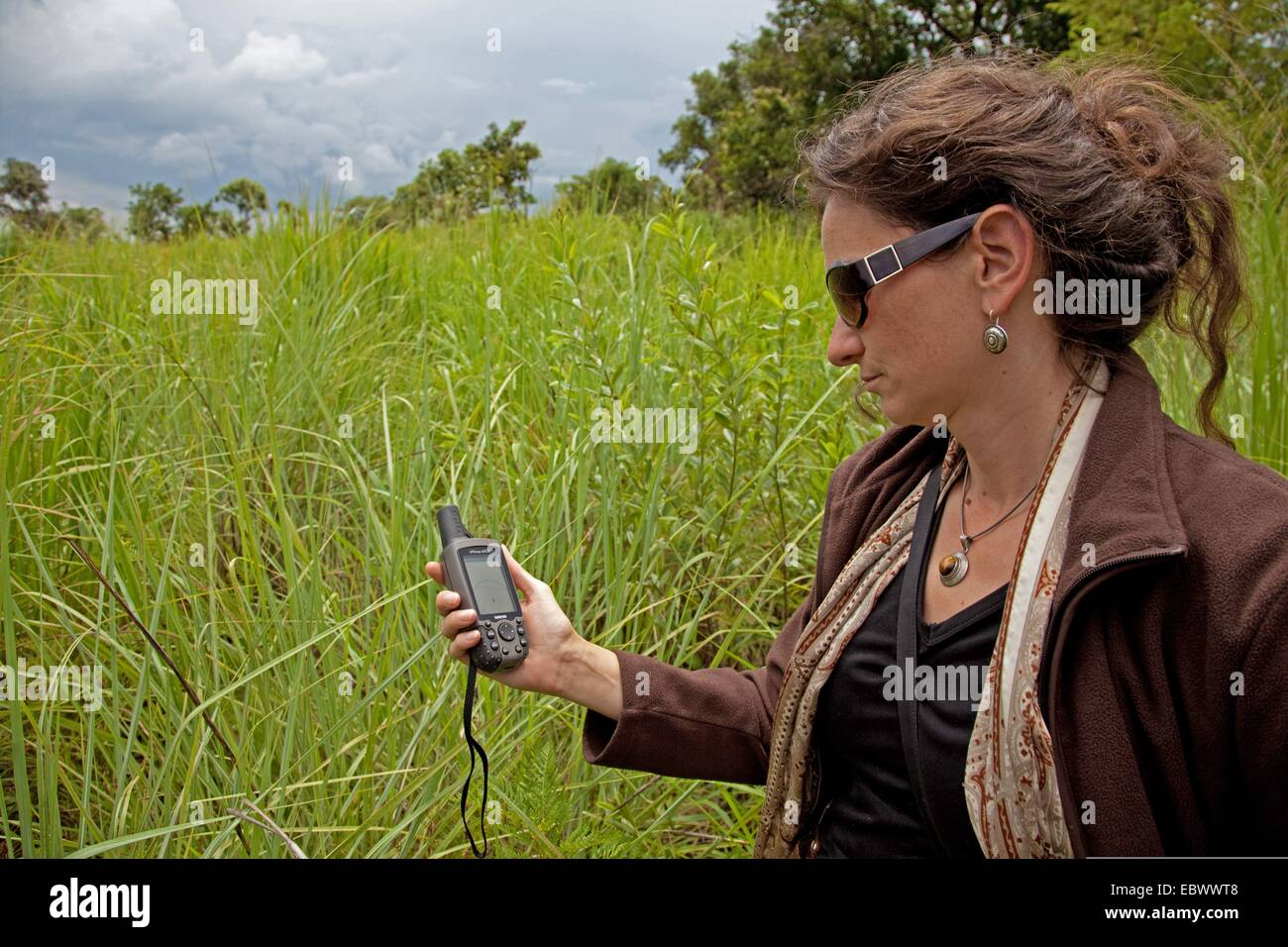 tourist orients herself with the help of a GPS computer at the 'National Parc de la Ruvubu' at the East - Stock Image