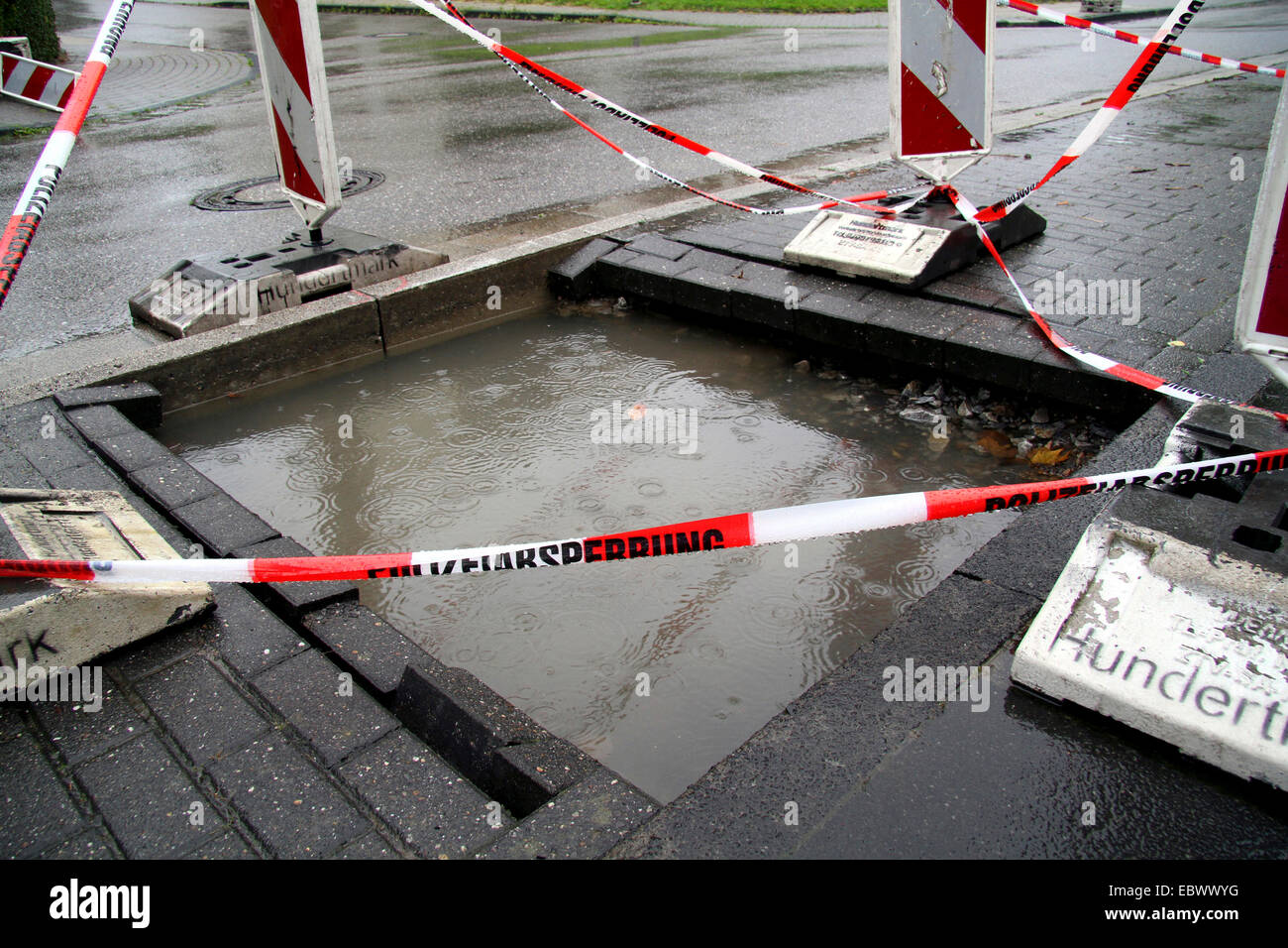 filled construction hole in duration rain, Germany - Stock Image