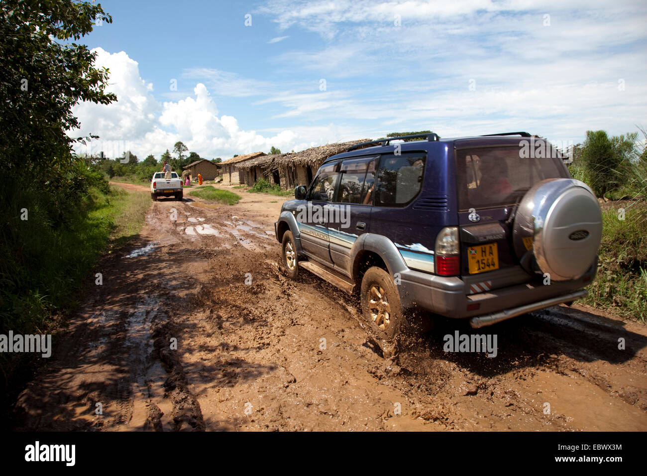 cross-country vehicles driving through a mud pit on a soil road through bush landscape passing humble huts, Burundi, - Stock Image
