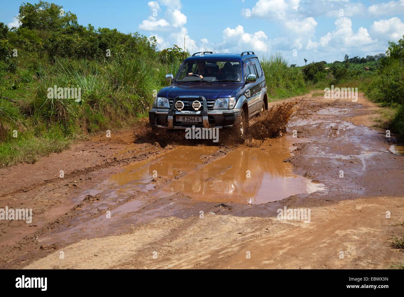 cross-country vehicle driving through a mud pit on a soil road through bush landscape, Burundi, Cankuzo, National - Stock Image