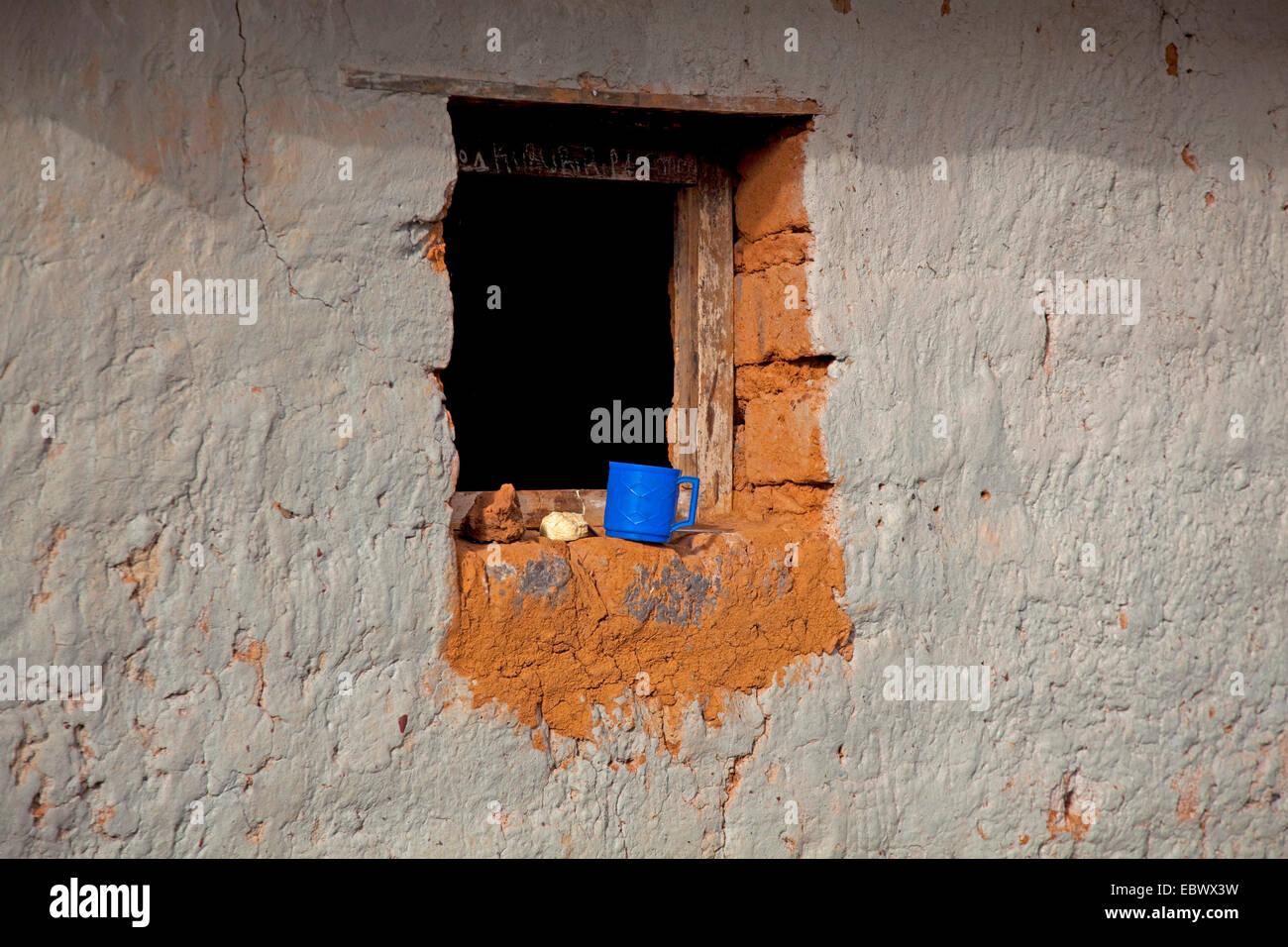 plastic cup standing on the windowsill of a simple mud brick house, Burundi, Cankuzo, Near National Parc de la Ruvubu, - Stock Image