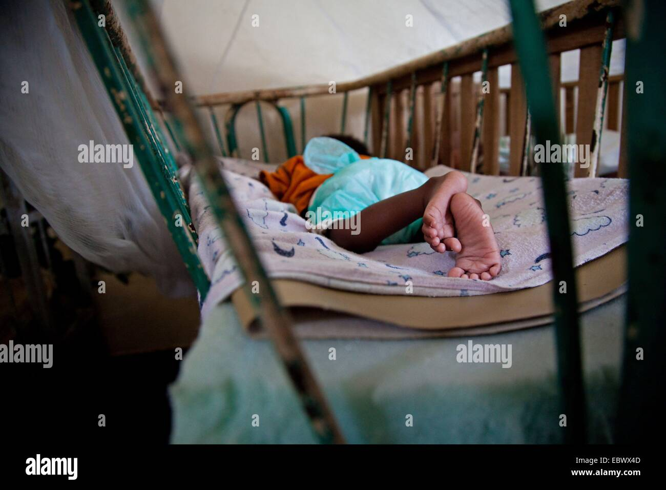 Baby In An Orphanage Sleeping In A Bed With Lattice Bars