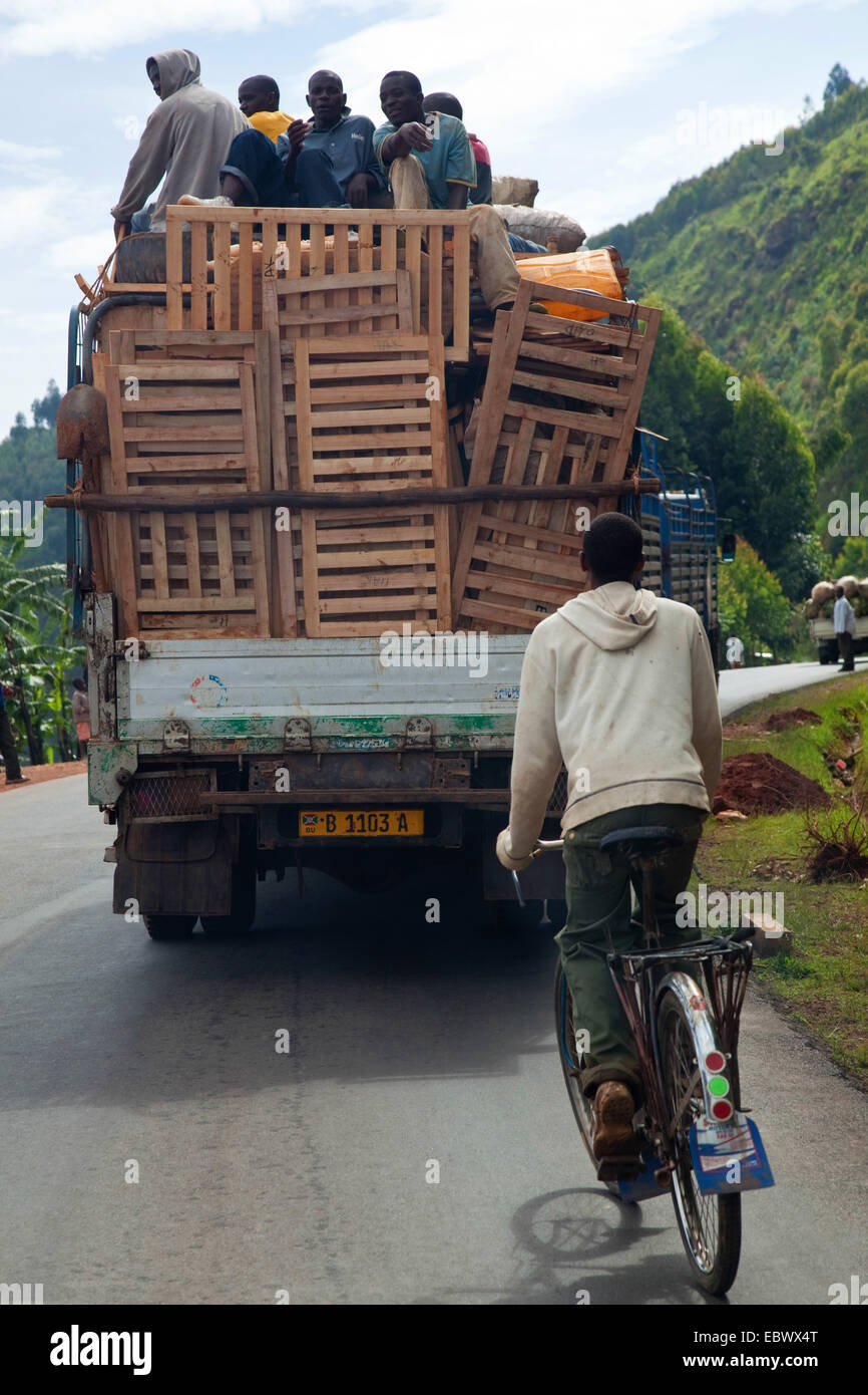 biker behind overloaded truck on winding road, Burundi, Karuzi, Buhiga - Stock Image