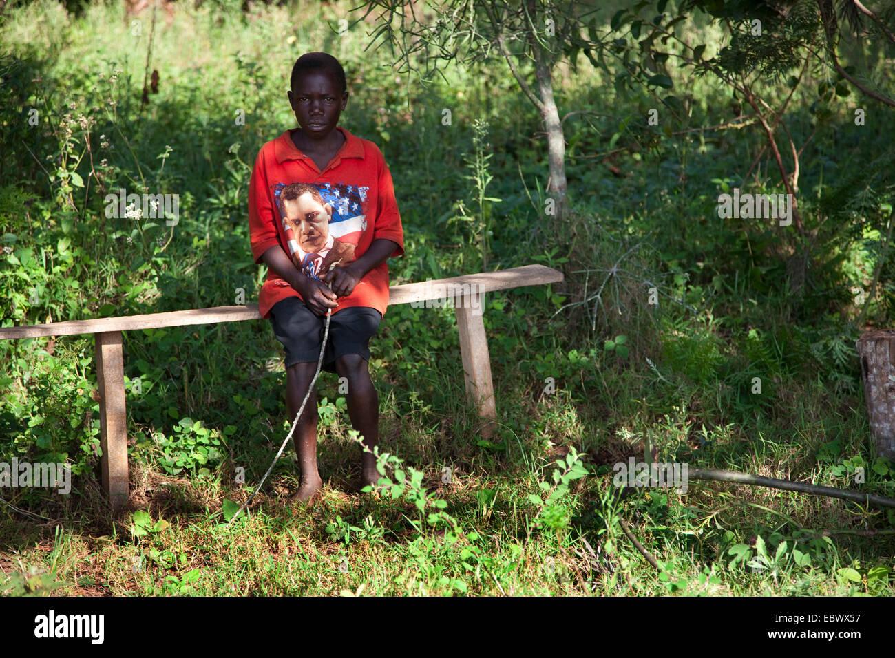 boy sitting on wooden bench, US president Obama is printed on his t-shirt, Burundi, Cankuzo, Cankuzo - Stock Image