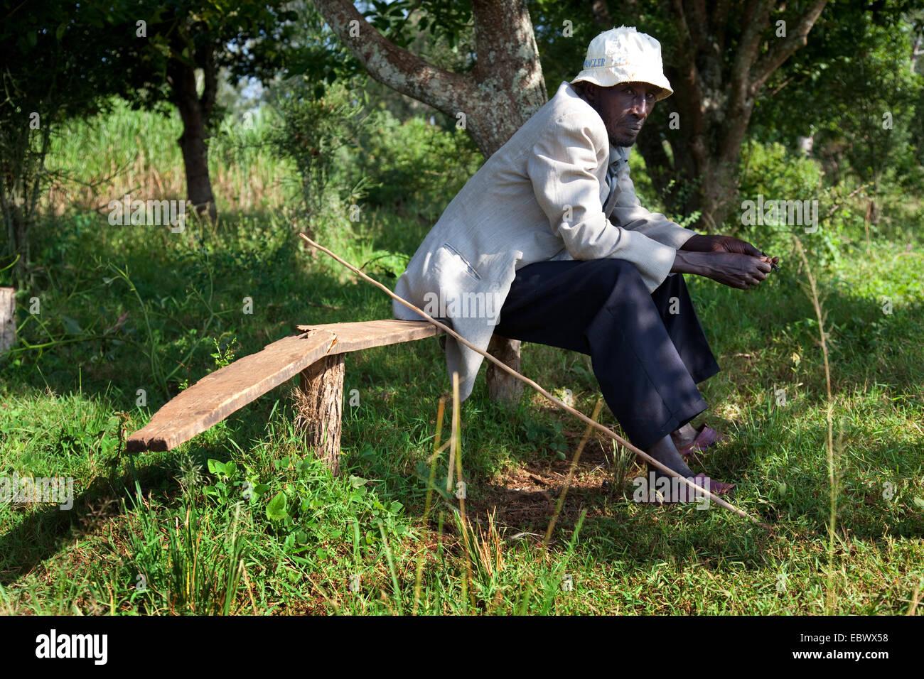 man with hat sitting on wooden bench, Burundi, Cankuzo, Cankuzo - Stock Image