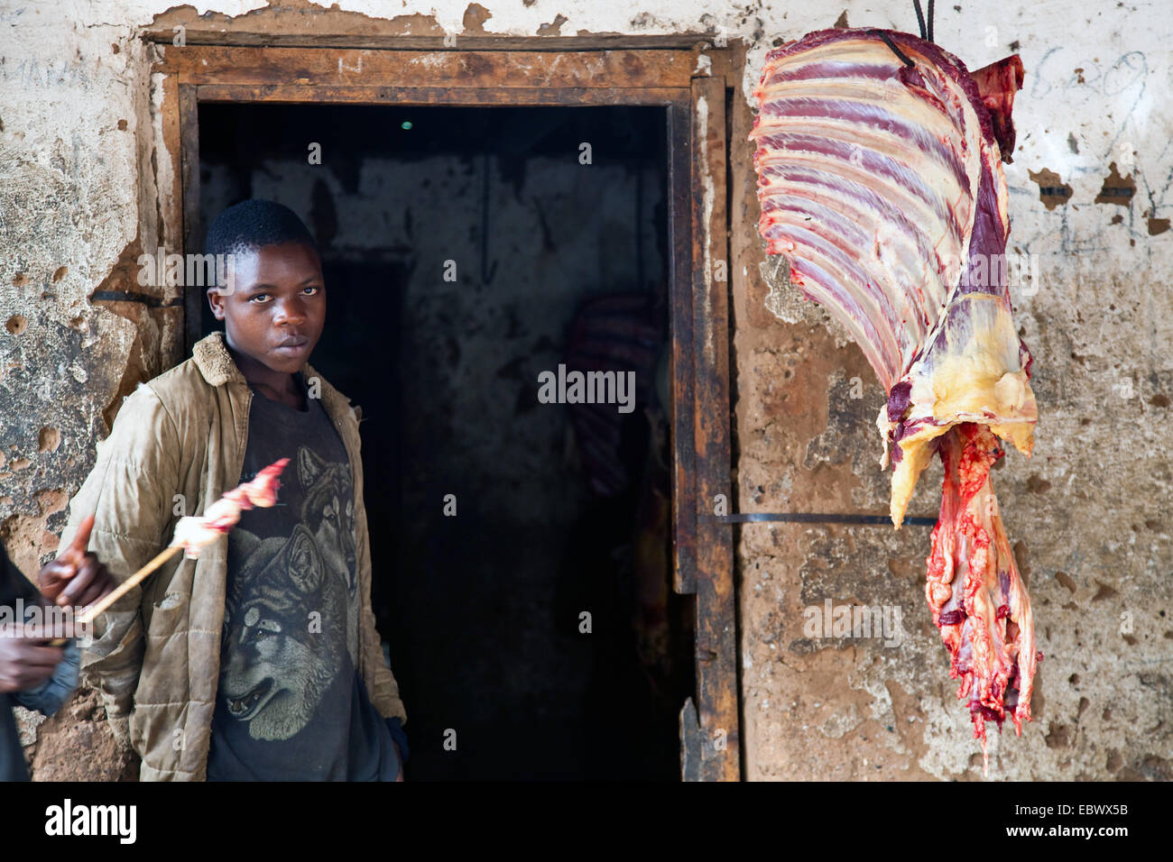 butcher at work, ribs of a cow hanging next entrance, Burundi, Bujumbura Rural, Bugarama Stock Photo