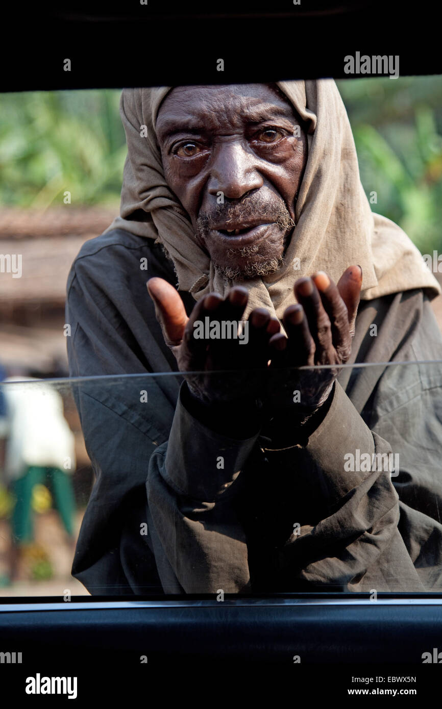 elderly man begging at open window of a car, Burundi, Bujumbura Rural, Bugarama - Stock Image
