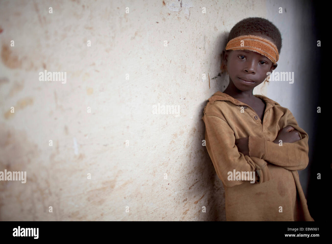 portrait of a young boy leaning against a house wall in a fishing village, Burundi, Nyanza Lac, Mvugo, Nyanza Lac - Stock Image