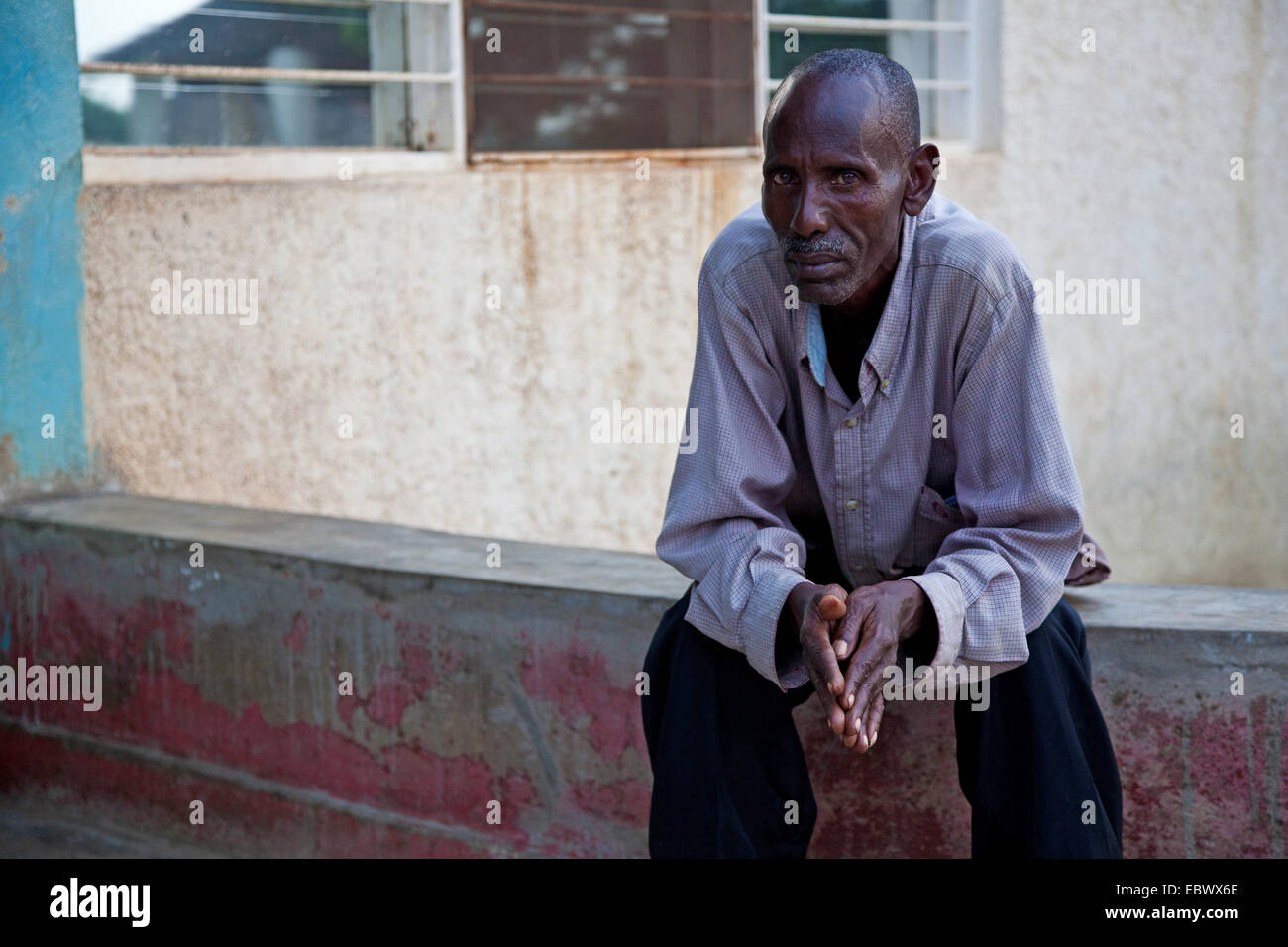 portrait of an old man in front of an orphanage in which he is taking care of children, Burundi, Bujumbura Marie, - Stock Image