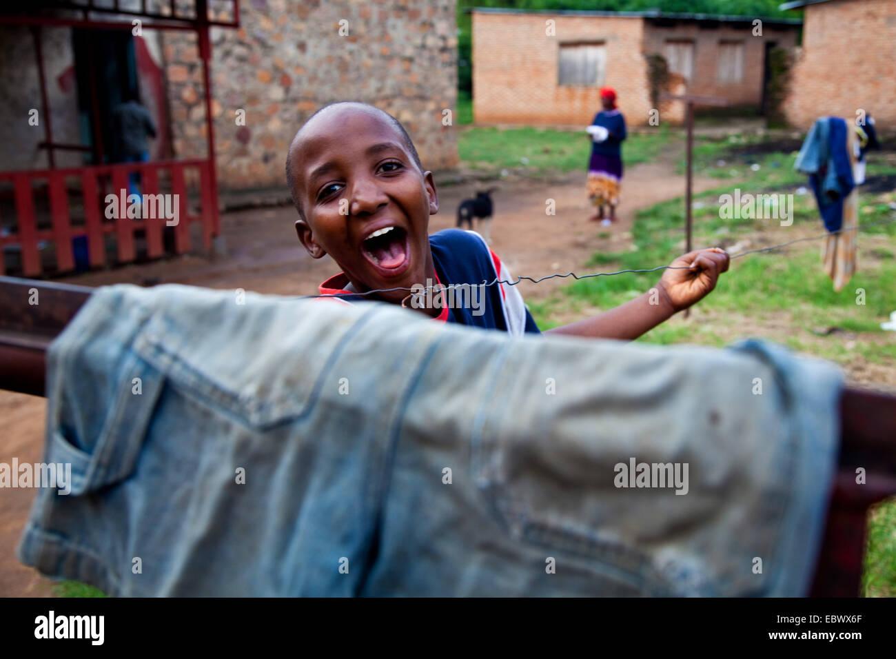 boy in a courtyard looking over a clothesline laughing, Burundi, Bujumbura Marie, Bujumbura - Stock Image