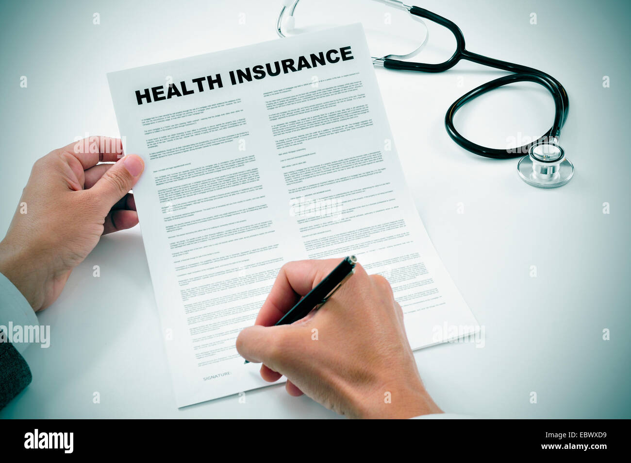 closeup of a young man signing a health insurance policy - Stock Image