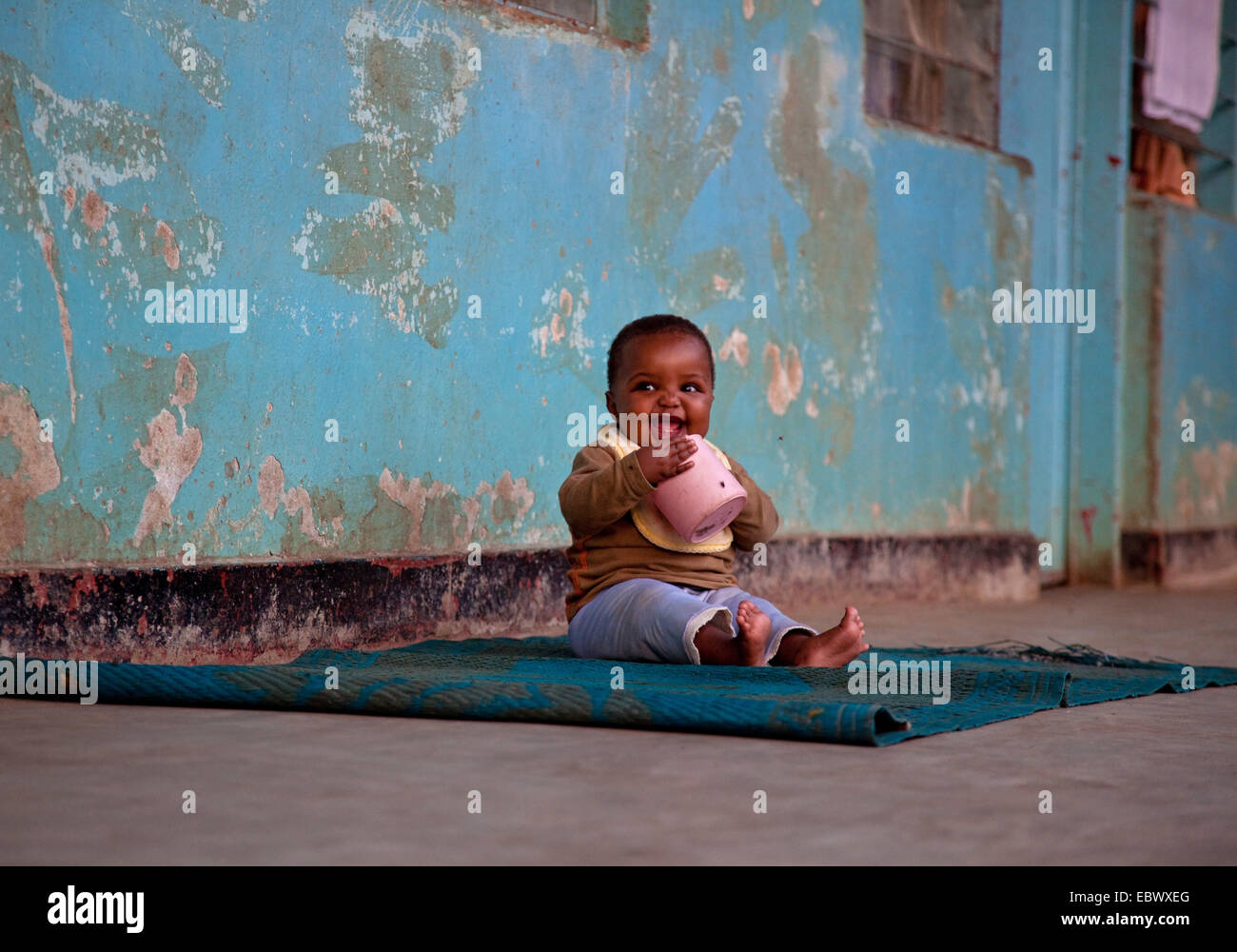 baby sitting on a carpet in front of the shabby wall of an orphanage sucking at a plastic pot, Burundi, Bujumbura - Stock Image