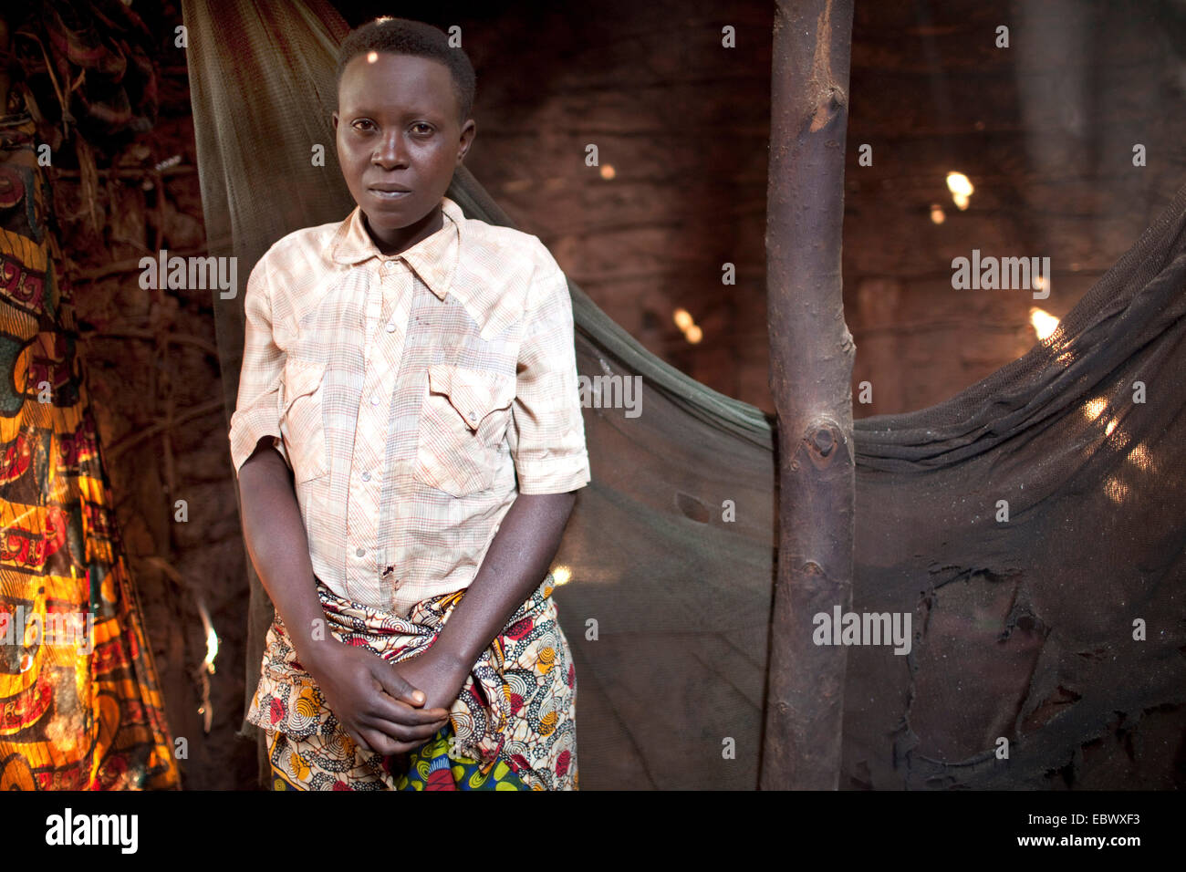 single mother with four children standing in front of damaged mosquito net in her little mud house, Burundi, Karuzi, - Stock Image