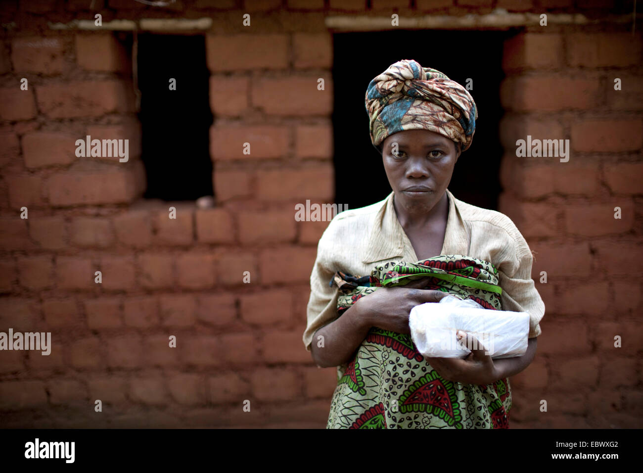woman in traditional clothes standing in front of a mud brick house under construction, Burundi, Karuzi, Buhiga - Stock Image