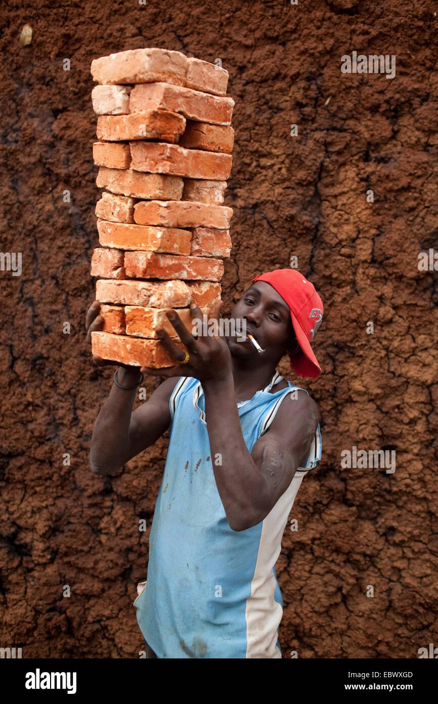 young man smoking a cigarette and carrying stack of bricks, Burundi, Karuzi, Buhiga - Stock Image
