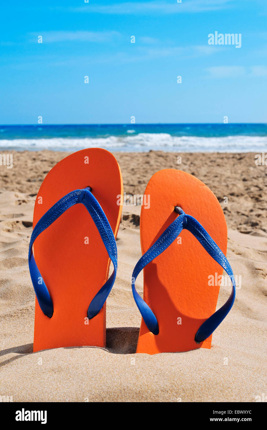a pair of orange flip-flops on the sand of a beach - Stock Image