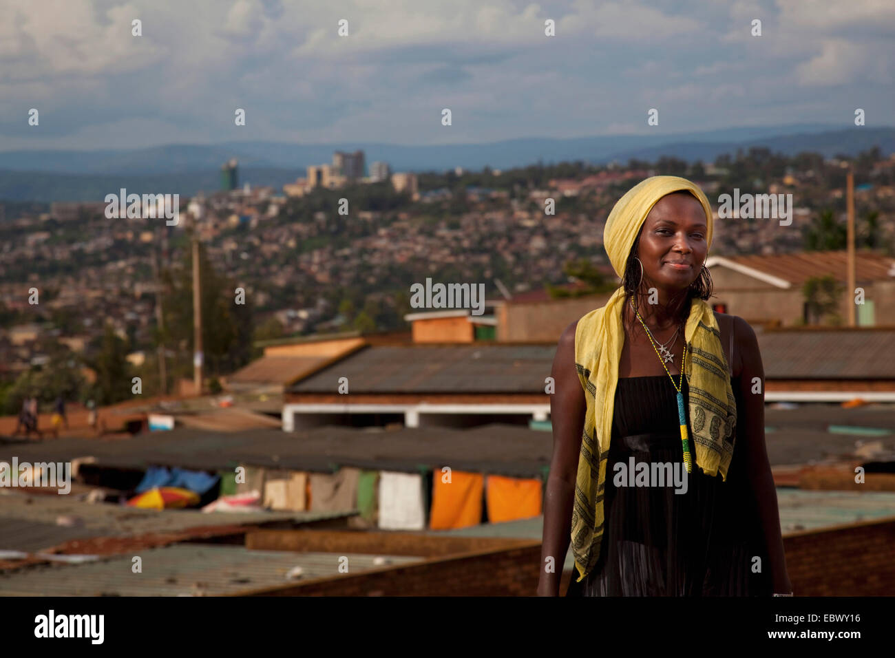 pretty young woman standing smiling in front city panorama with poorer and richer quarters contrasting, Rwanda, - Stock Image