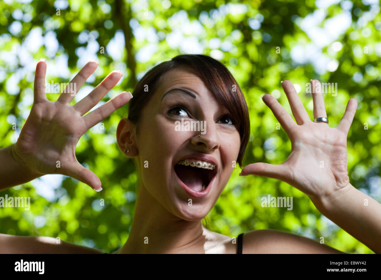 young woman with brackets makes a face Stock Photo