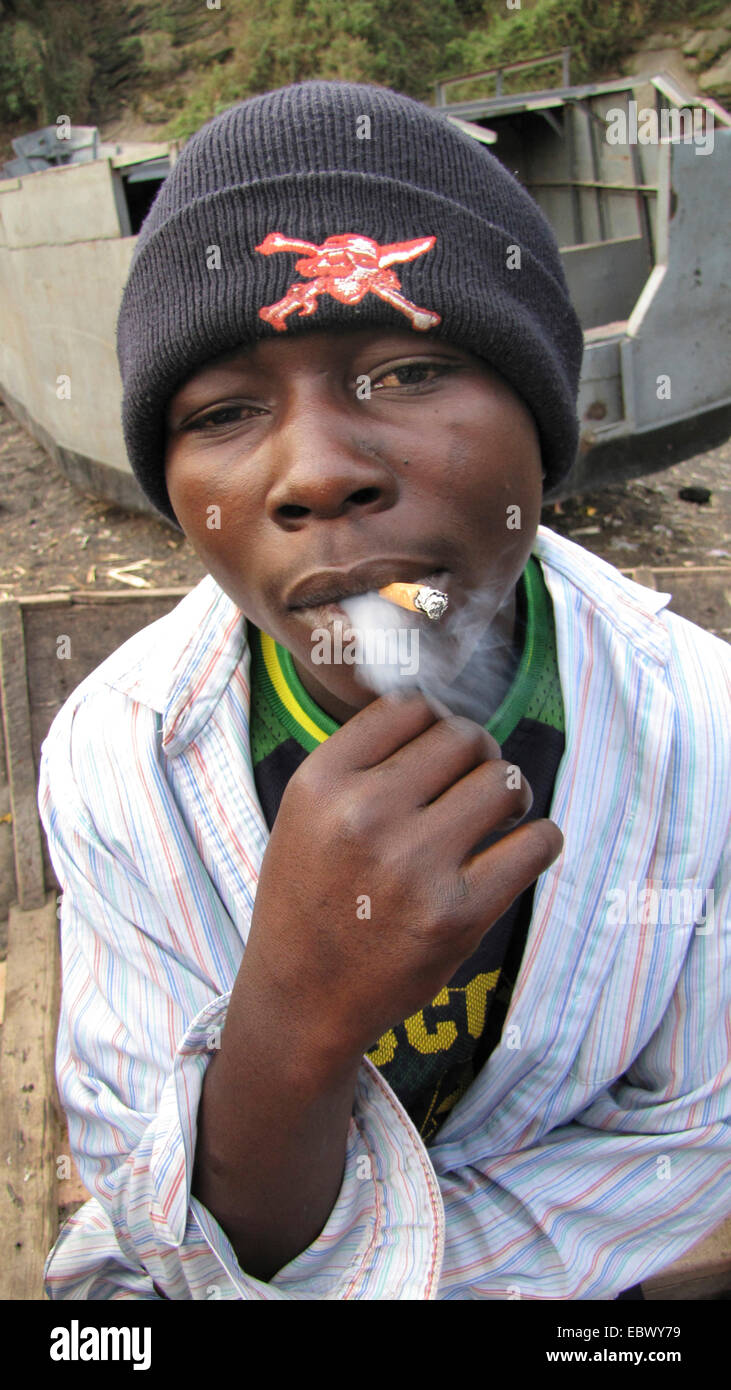 teenager drug addict with reddened eyes smoking a cigarette near the harbour of Goma, Republic of the Congo, North - Stock Image