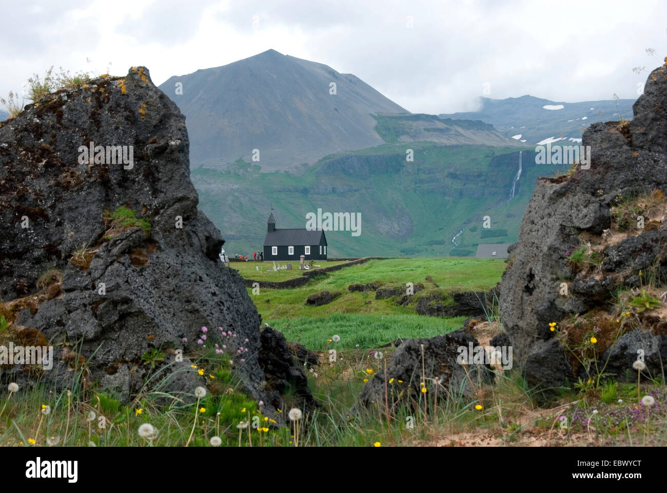 view through two rocks of the lava field 'Budahraun' at the little wooden church 'Budirkirkja' in - Stock Image