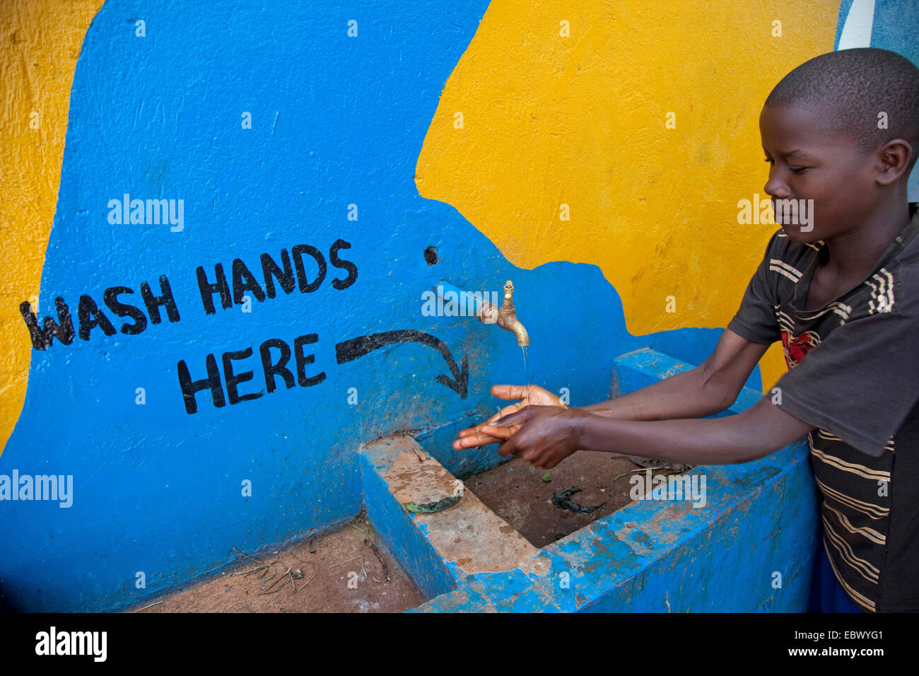 boy is washing his hands at a tap, the painted words on the wall say 'wash hands here', Uganda, Jinja - Stock Image