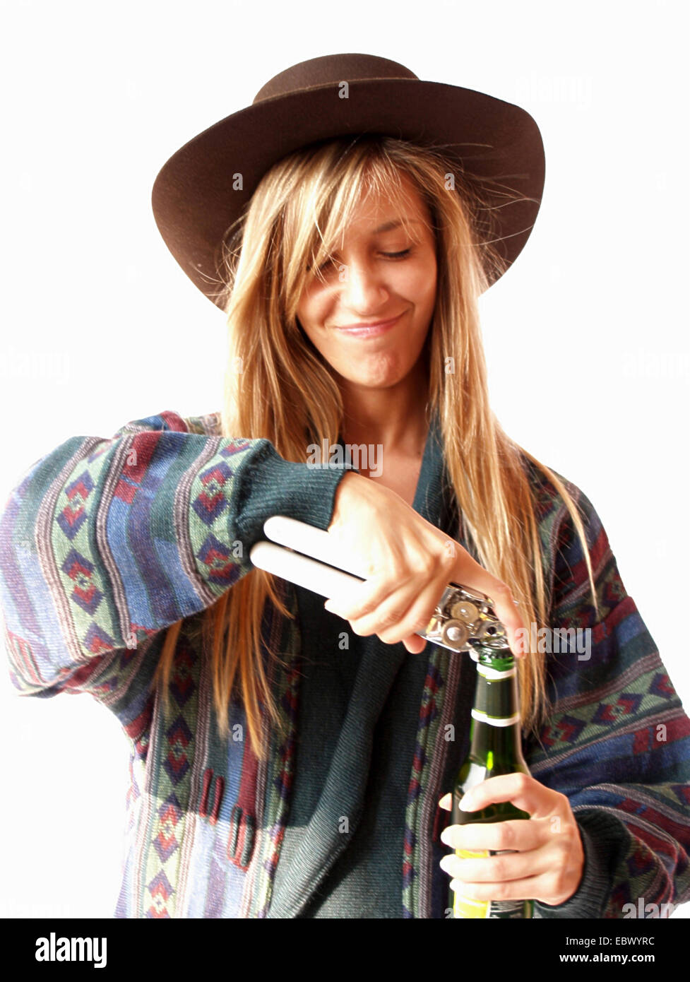 longhaired blond young woman wearing a wide-brimmed hat and a colourfully patterned jersey is opening a bottle with Stock Photo