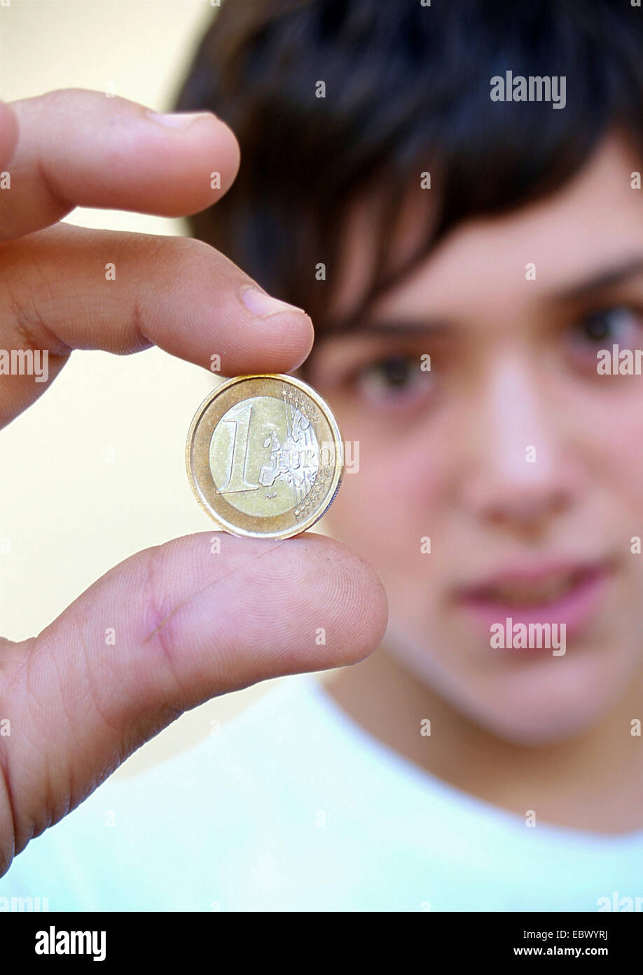 young man holding a 1 Euro coin between the fingers - Stock Image