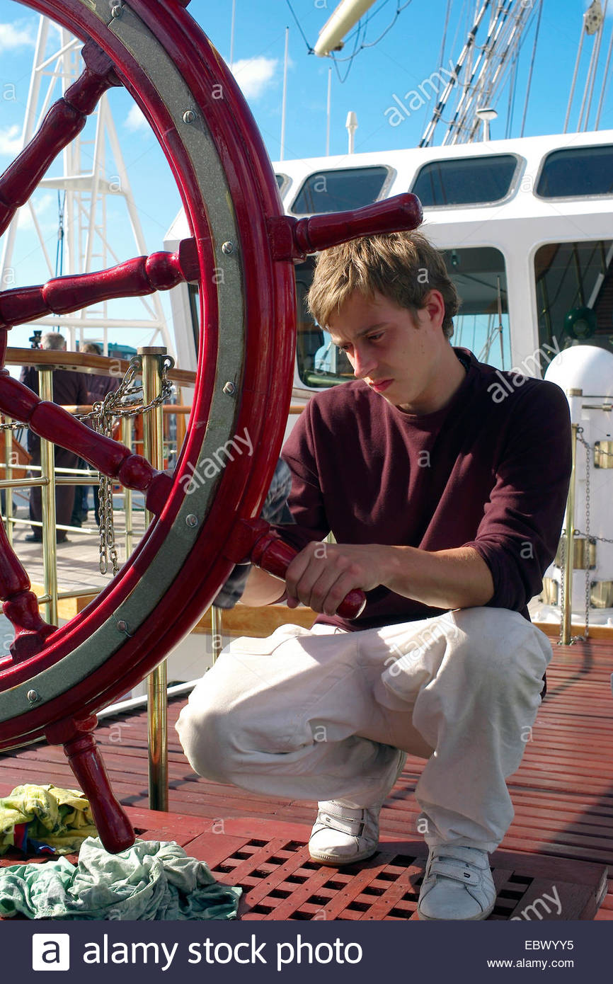 cate on deck of a training ship cleaning the wheel - Stock Image