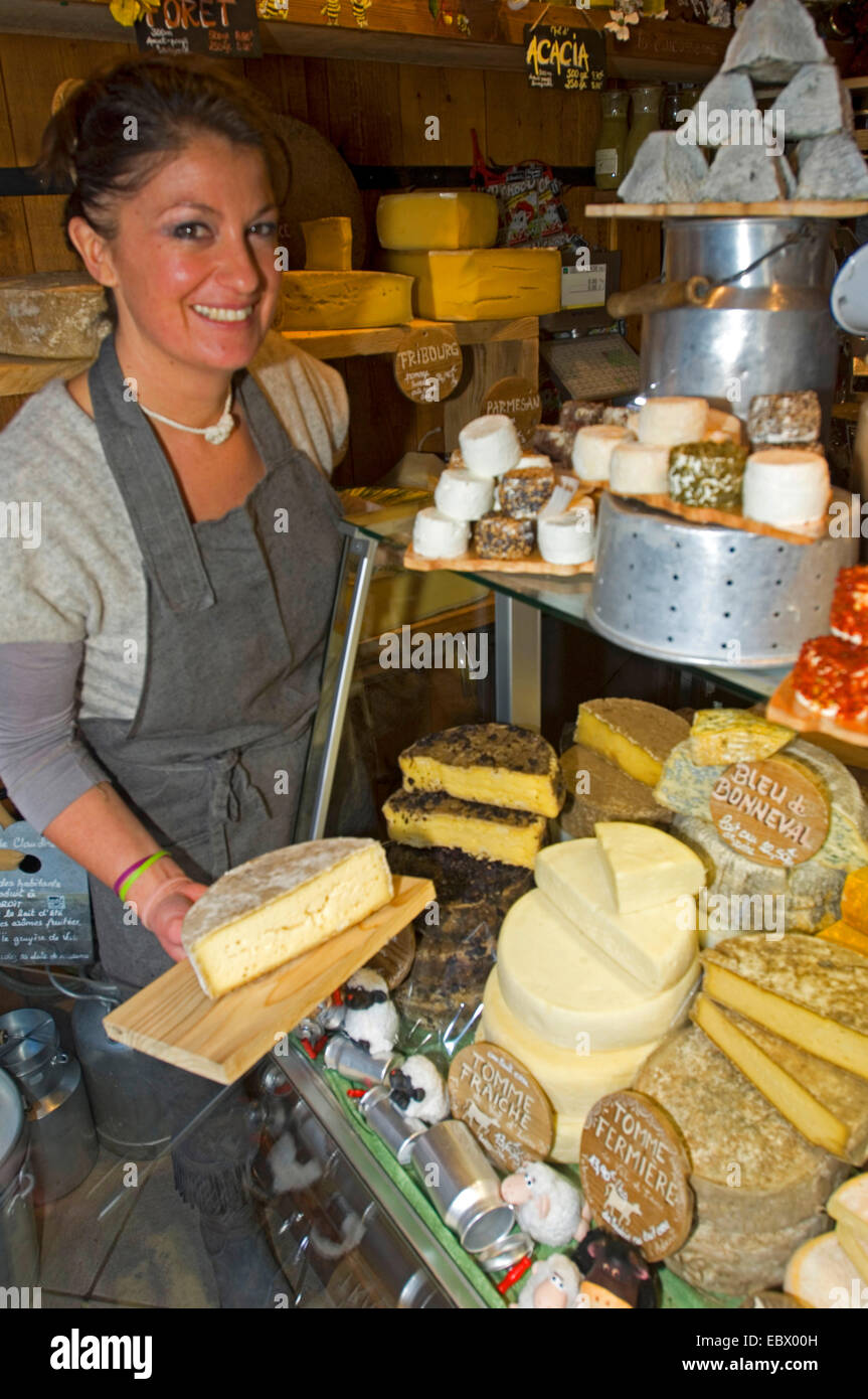 chese shop seller presenting her goods with a smile, France, Savoie, Val d' Is�re - Stock Image