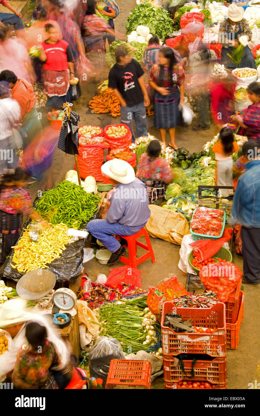 Local vendors in unusual birdseye angle from above with blurred movement in colorful printed clothes in fruit shopping - Stock Image