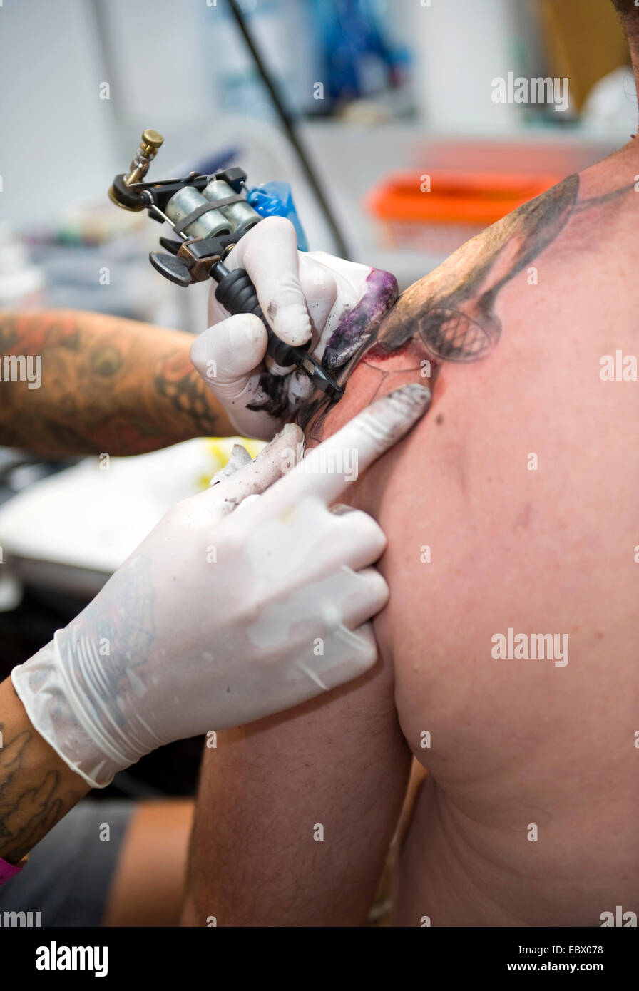 tattooing of a back of a man - Stock Image