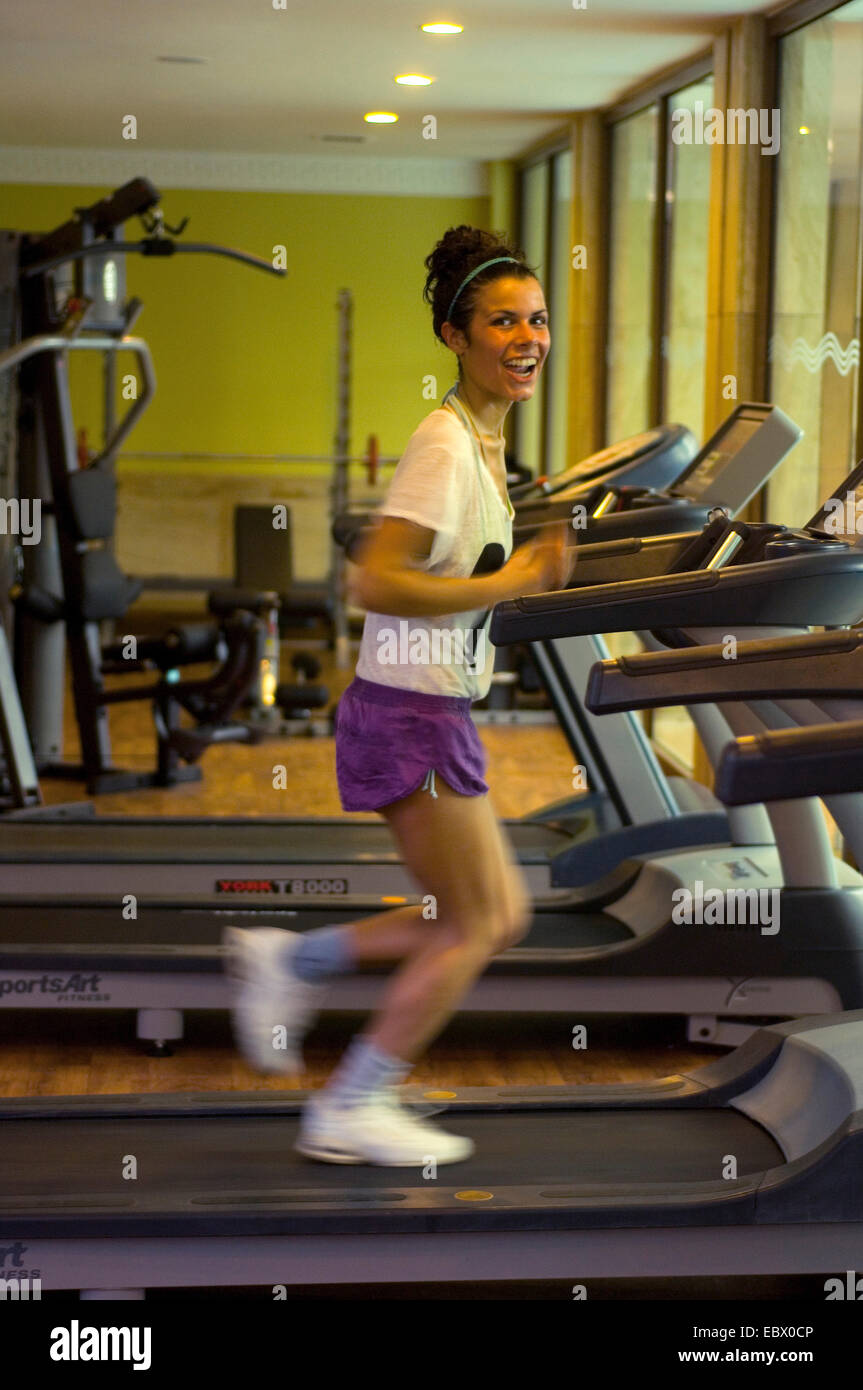 young girl at a fitness center laughing while runing on a treadmill - Stock Image
