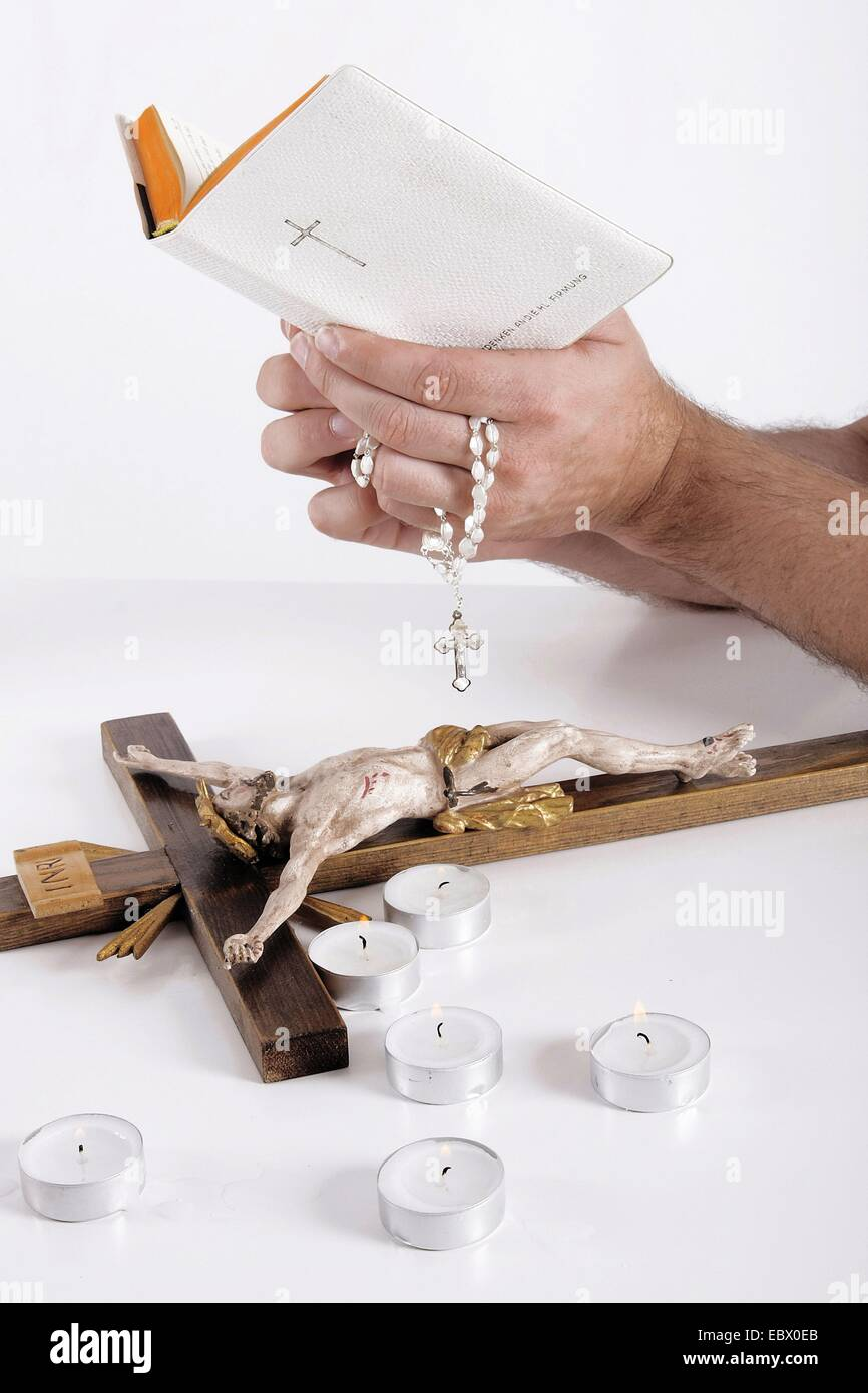 bible in the hand of a man, christian things on a desk - Stock Image
