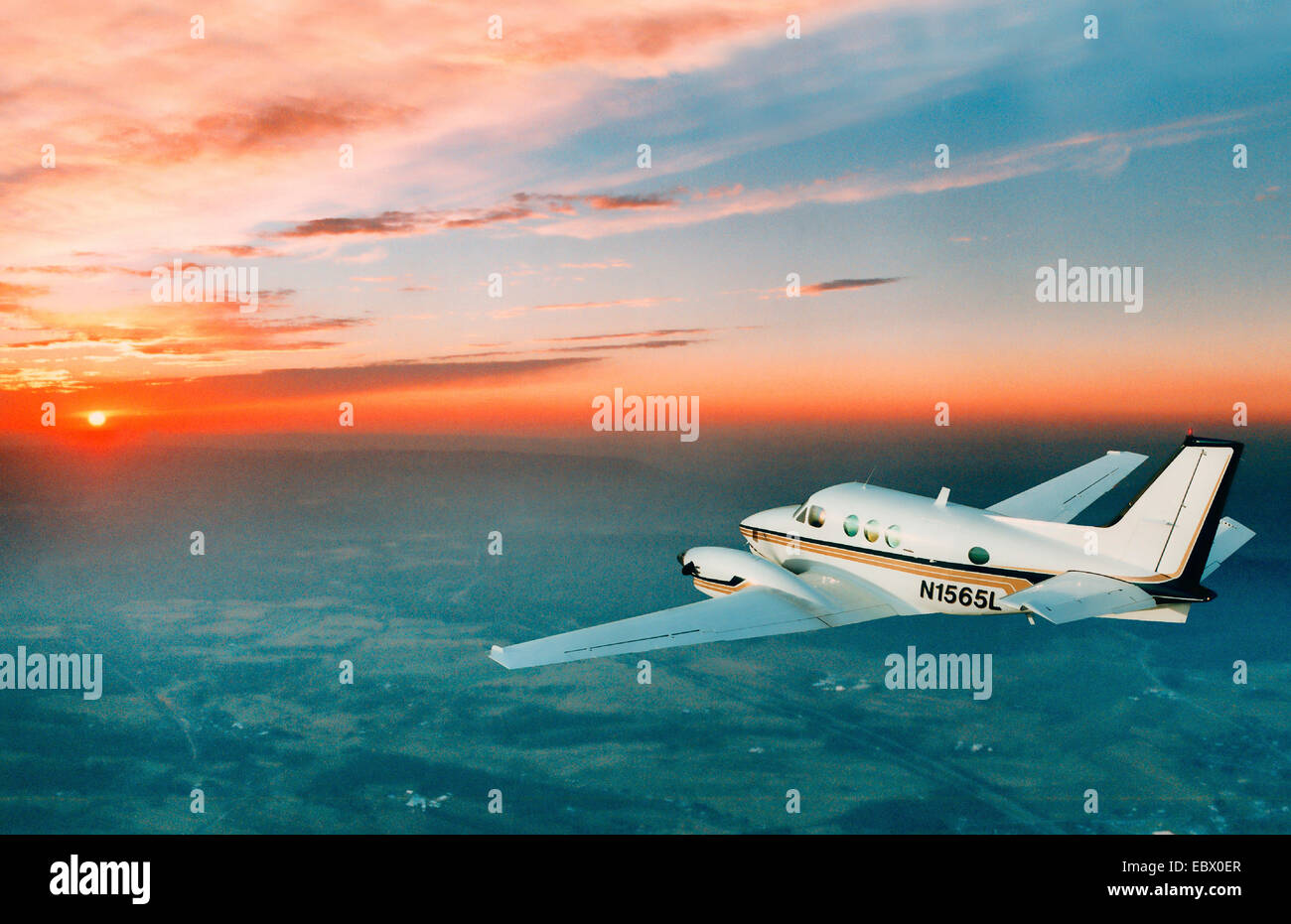 a small twin engine commuter plane flying into the beautiful orange sunset - Stock Image