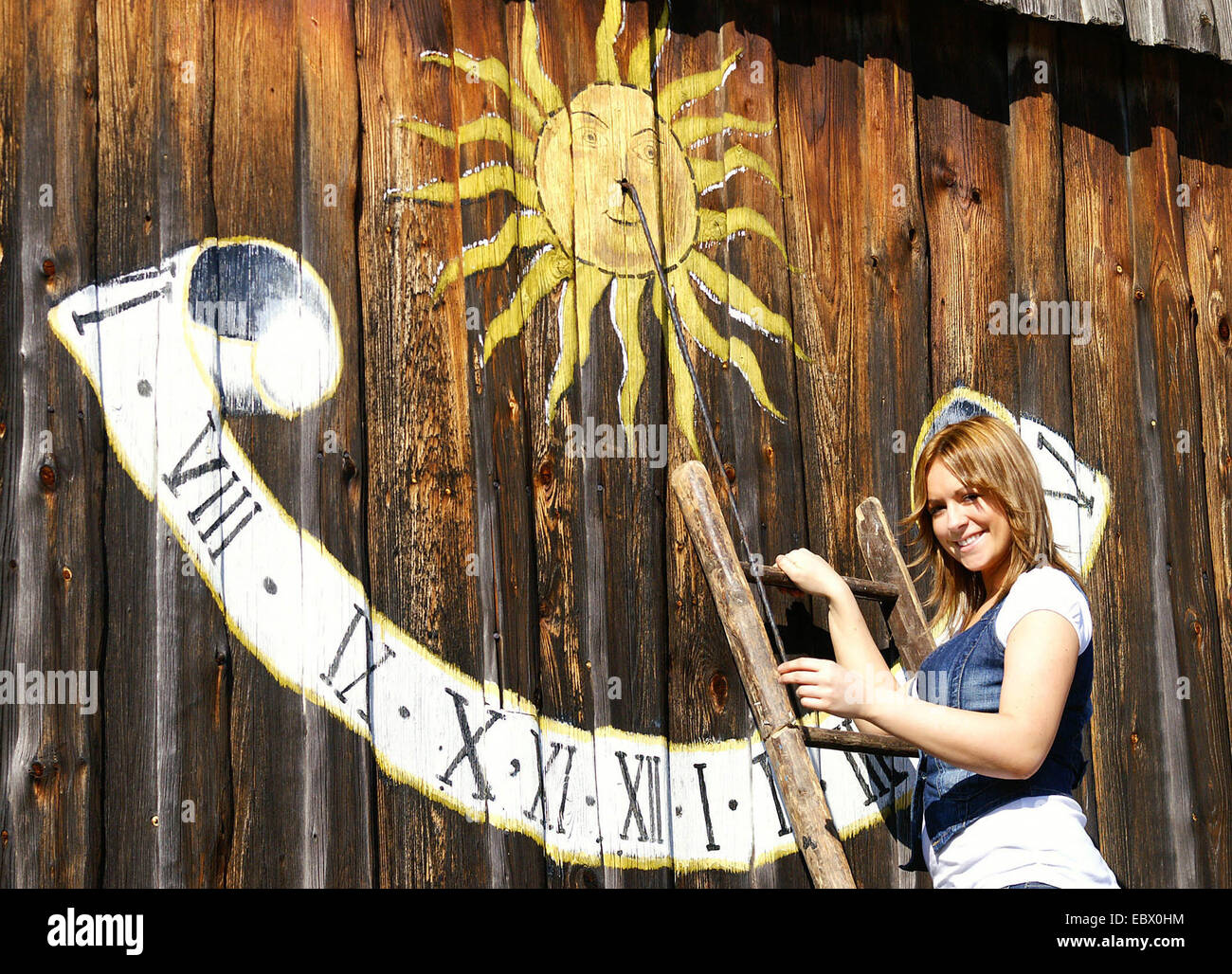 smiling longhaired blond young woman standing on a ladder leaned against a palisade trench with a sundial painted Stock Photo