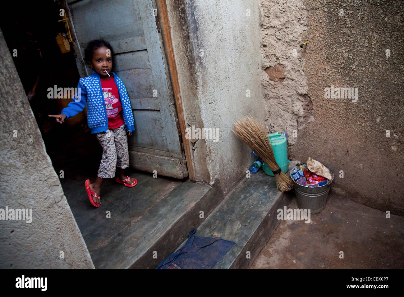 small girl in a poorer area of the capital city waves into the house as guests approach, Rwanda, Nyamirambo, Kigali - Stock Image