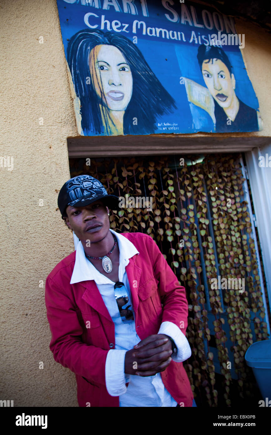 young man in front of a barber shop that he just visited, named 'Chez Maman Aisha' , Rwanda, Nyamirambo, - Stock Image