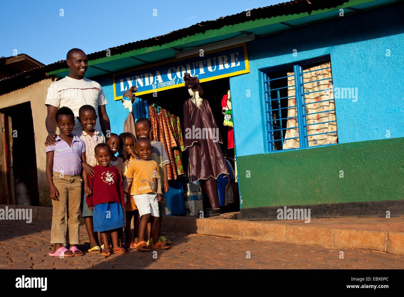 Tailer standing in front of his atelier with a group of children from the neighborhood, Rwanda, Nyamirambo, Kigali - Stock Image